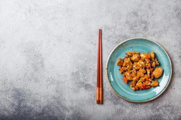 Bovenaanzicht van kung pao-kip op bord klaar om te eten, ruimte voor tekst. gewokt chinees traditioneel gerecht met kip, pinda's, groenten, chilipepers. chinees diner, eetstokjes, stenen achtergrond
