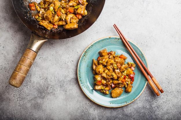 Bovenaanzicht van kung pao-kip op een bord klaar om te eten. gewokt chinees traditioneel gerecht met kip, pinda's, groenten, chilipepers. chinees diner, eetstokjes, rustieke betonnen achtergrond