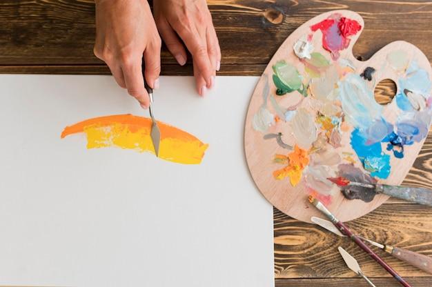Bovenaanzicht van kunstenaar met behulp van gereedschap om te schilderen