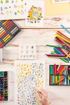 Bovenaanzicht van kunstenaar tekening bloemen ontwerp op werkplek