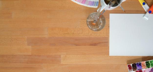 Bovenaanzicht van kunstenaar werkplek met schets papier en water kleuren op houten tafel