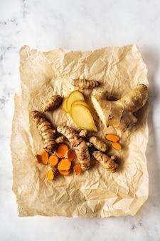 Bovenaanzicht van kurkuma wortels en gember op verfrommeld papier en wit oppervlak