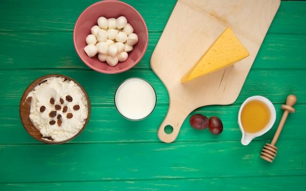 Bovenaanzicht van kwark in een kom gegarneerd met mozarella rozijnen en een stuk nederlandse kaas op houten snijplank met honing op groen hout