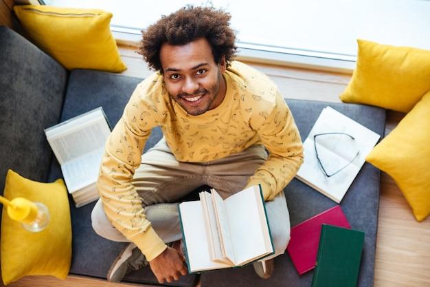Bovenaanzicht van lachende afro-amerikaanse jongeman die thuis een boek leest