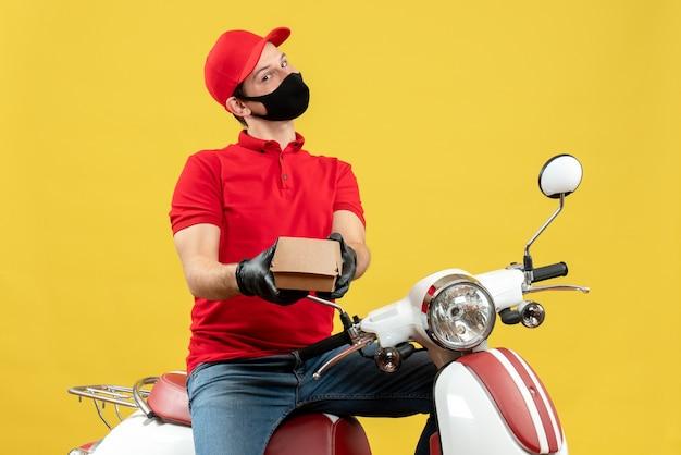 Bovenaanzicht van lachende bezorger dragen uniform en hoed handschoenen in medische masker zittend op scooter bevel geven