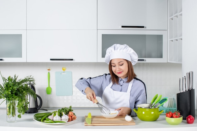 Bovenaanzicht van lachende chef-kok en verse groenten met kookgerei en het mengen van het ei in een witte kom in de witte keuken