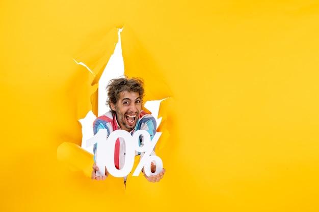 Bovenaanzicht van lachende en emotionele bebaarde man met tien procent in een gescheurd gat in geel papier