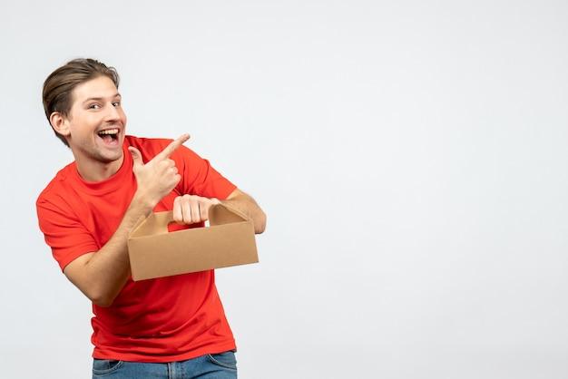Bovenaanzicht van lachende en emotionele jonge man in rode blouse met doos iets aan de linkerkant op witte muur te wijzen