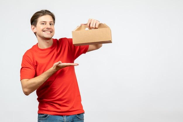 Bovenaanzicht van lachende en gelukkige jonge man in rode blouse met doos op witte muur