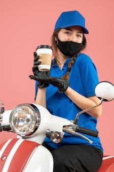 Bovenaanzicht van lachende gelukkige vrouwelijke koerier met een zwart medisch masker en handschoenen die bestellingen op perzik afleveren