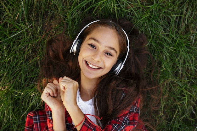 Bovenaanzicht van lachende jonge brunette meisje liggend op gras