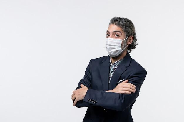 Bovenaanzicht van lachende jonge kerel in pak met masker en schouderophalend op witte achtergrond