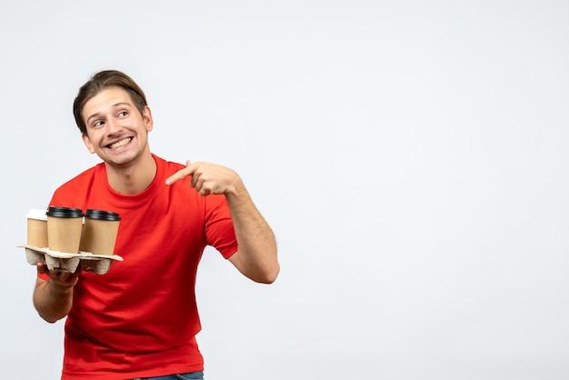 Bovenaanzicht van lachende jonge man in rode blouse bestellingen op witte muur te wijzen
