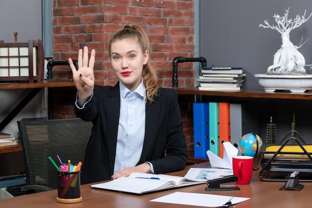 Bovenaanzicht van lachende jonge vrouw die aan een tafel zit en vier op kantoor laat zien