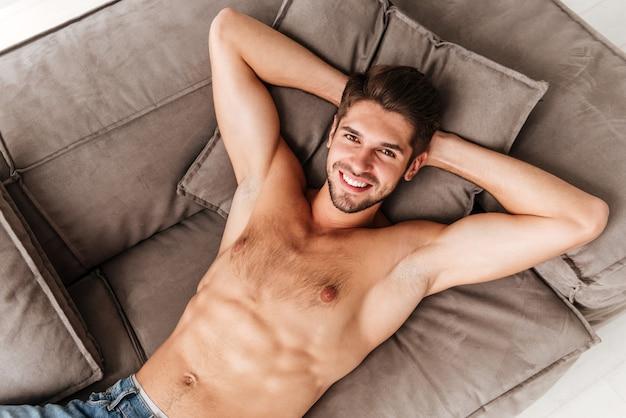 Bovenaanzicht van lachende ontspannen jonge man liggend op de bank thuis