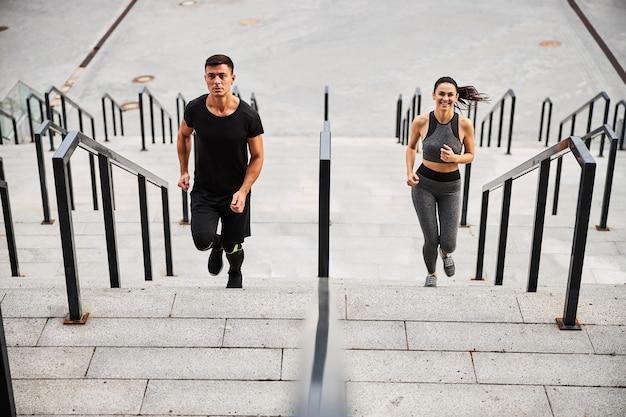Bovenaanzicht van lachende slanke vrouw en atletische man in outfit die samen naar stedelijk gebouw loopt