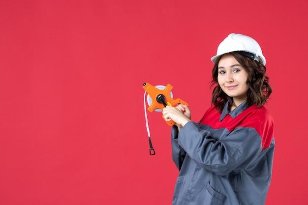 Bovenaanzicht van lachende vrouwelijke architect in uniform met harde hoed met meetlint op geïsoleerde rode achtergrond