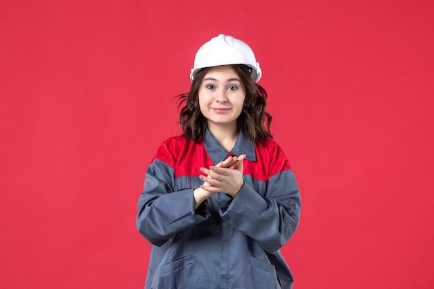 Bovenaanzicht van lachende vrouwelijke bouwer in uniform met harde hoed en applaus op geïsoleerde rode achtergrond