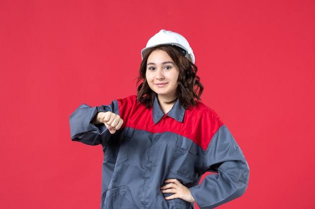 Bovenaanzicht van lachende vrouwelijke bouwer in uniform met harde hoed en het controleren van haar tijd op geïsoleerde rode achtergrond
