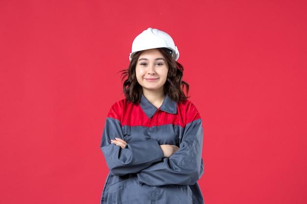 Bovenaanzicht van lachende vrouwelijke bouwer in uniform met harde hoed op geïsoleerde rode achtergrond