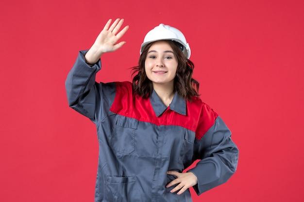 Bovenaanzicht van lachende vrouwelijke bouwer in uniform met helm die hallo zegt tegen iemand op geïsoleerde rode achtergrond