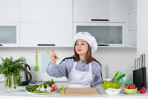 Bovenaanzicht van lachende vrouwelijke chef-kok en verse groenten met kookgerei en naar voren wijzend in de witte keuken