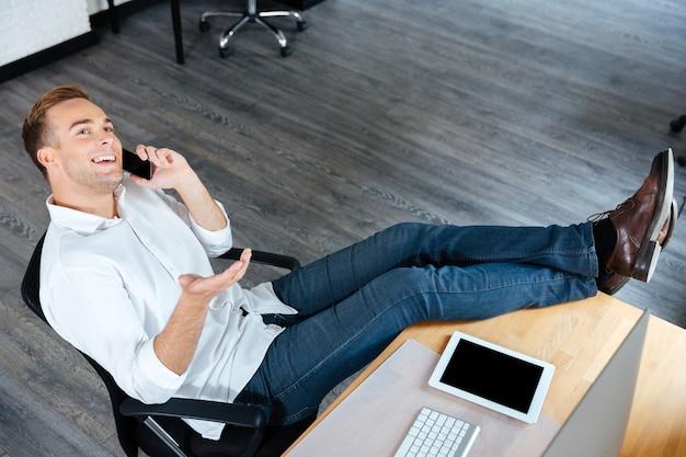 Bovenaanzicht van lachende zelfverzekerde jonge zakenman zittend en pratend op mobiele telefoon op de werkplek