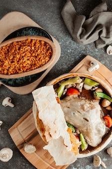 Bovenaanzicht van lamsstoofpot bedekt met flatbread geserveerd met bulgur