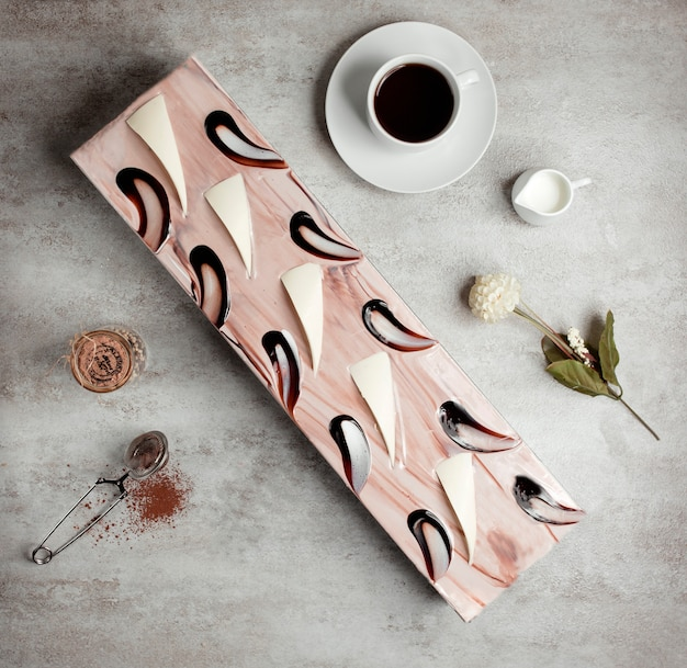 Bovenaanzicht van lange cake versierd met koffie siroop en witte chocolade