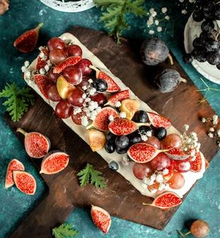 Bovenaanzicht van lange taart versierd met varkens en druiven
