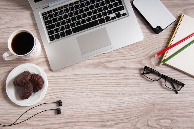 Bovenaanzicht van laptop en kladblok met bril en koptelefoon op rustieke houten bureaublad en kopje koffie.