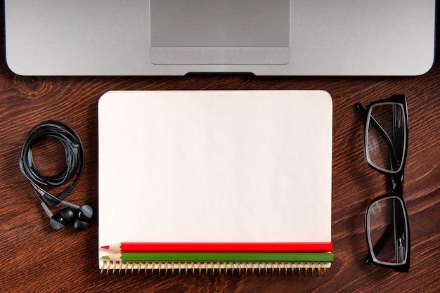 Bovenaanzicht van laptop en kladblok met bril en koptelefoon op rustieke houten bureaublad.