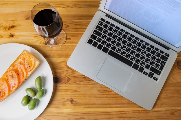 Bovenaanzicht van laptop en licht avondbrood, olijven en wijn. plat lag concept van diner en laptop computercombinatie op natuurlijke houten achtergrond