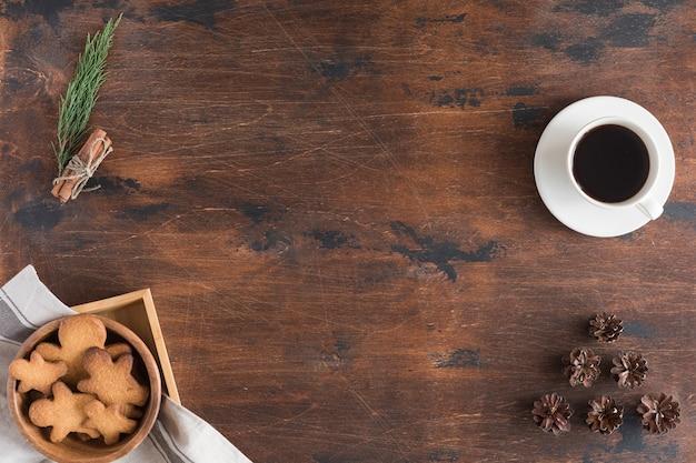 Bovenaanzicht van laptop, gingerbread man, kopje koffie op donkere rustieke houten achtergrond