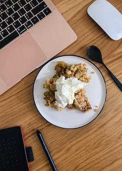 Bovenaanzicht van laptop, grafisch tablet, mond en een cake met ijs