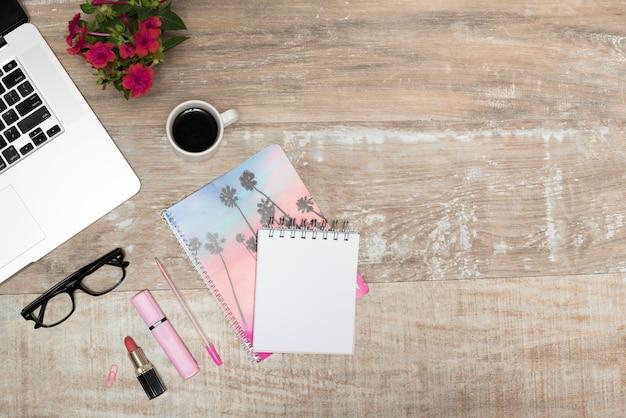 Bovenaanzicht van laptop; lippenstift; markeerstift; spiraalvormige blocnote; koffiekop; pen; en lenzenvloeistof op houten bureaulijst