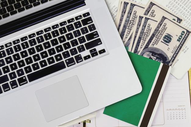 Bovenaanzicht van laptop met boekenbank en bankbiljetten