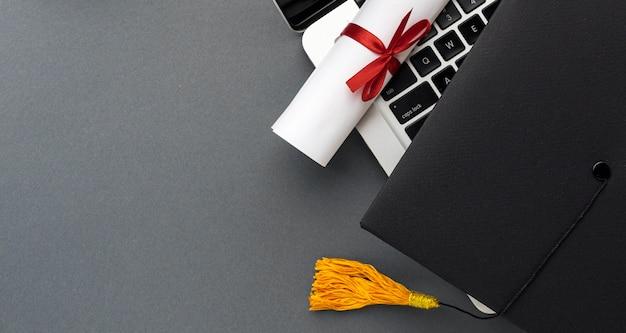 Bovenaanzicht van laptop met diploma en academische pet