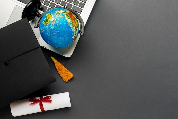 Bovenaanzicht van laptop met diploma en globe