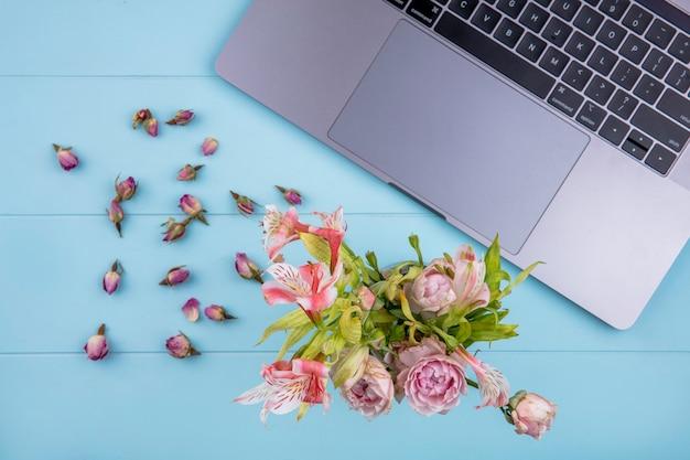 Bovenaanzicht van laptop met een boeket van lichtroze bloemen op een blauwe ondergrond