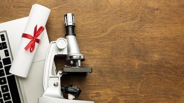 Bovenaanzicht van laptop met microscoop en diploma