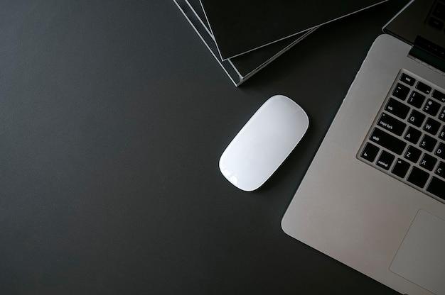Bovenaanzicht van laptop met muis en boeken op zwart lederen boven tafel.