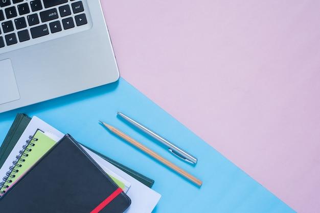 Bovenaanzicht van laptop, notebook, pen, potlood op blauwe en roze pastel kleur bakcground