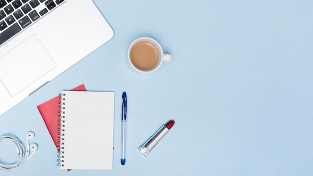 Bovenaanzicht van laptop; oortelefoons; lege kladblok; pen; lippenstift en kopje een thee op blauwe achtergrond