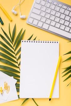 Bovenaanzicht van laptop op bureau met bladeren