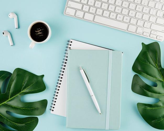 Bovenaanzicht van laptop op bureau met koffie en bladeren