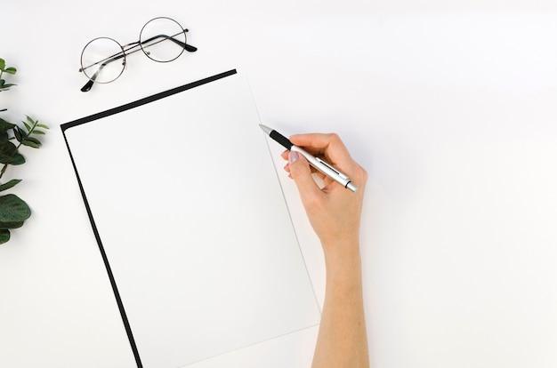 Bovenaanzicht van laptop op bureaublad met hand en bril