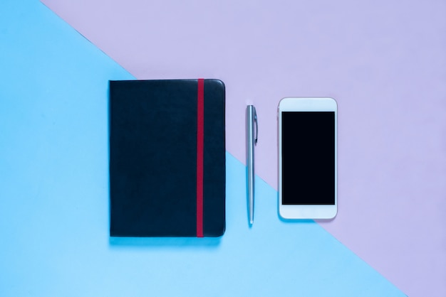 Bovenaanzicht van laptop, pen op blauwe en roze pastel kleur bakcground