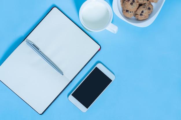 Bovenaanzicht van laptop, smartphone, cookie, laptop, melk op blauwe en roze pastel kleur bakcground