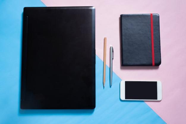 Bovenaanzicht van laptop, smartphone, laptop, pen, potlood op blauwe en roze pastel kleuren bakcground